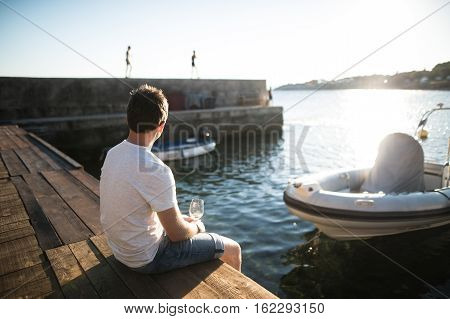 Handsome young man enjoying time at seaside, sitting on wooden pier, holding glass of white wine. Rear view.