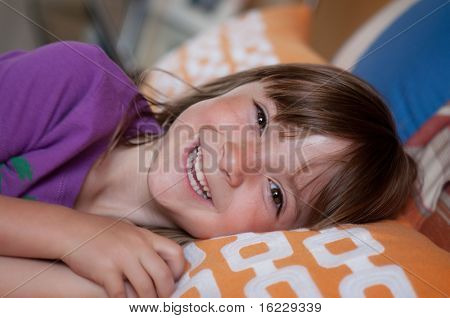 Sweet cute happy little girl smiling with delight while lying in bed.