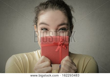 Girl hiding her smile behind a small red gift box
