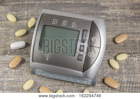 Digital sphygmomanometer blood pressure monitor on the background of wooden table. Tonometer and tablets