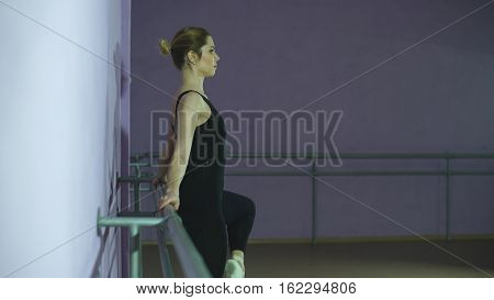 ballerina stretches herself near barre in the classroom