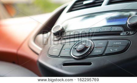 Transportation vehicle and car auto audio radio concept - Close up radio band button and radio stereo system on car panel with flare light effect and copy space
