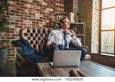 Exhausted man is sitting on couch and untying necktie. He holding mobile
