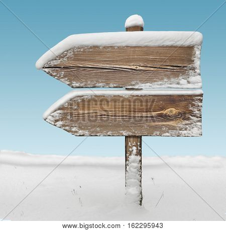 Wooden direction sign with snow on it and with sky on background. two arrows in one direction