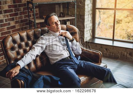 Exhausted businessman is sitting on couch and trying to take off necktie. His glance full of desperation