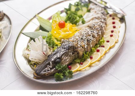 Stuffed pike decorated with vegetables and the greens. Very beautiful restaurant dish.