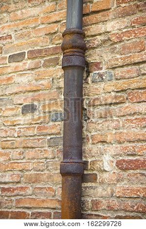 Detail of a downpipe against a brick wall - (Tuscany - Italy)