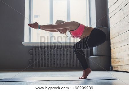 Young slim blond woman in yoga class making asana exercises. Girl do vinyasa transition to pose. Healthy lifestyle in fitness club. Stretching in standing position