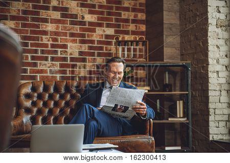 Hilarious businessman is sitting on couch, he is reading a newspaper with merry smile