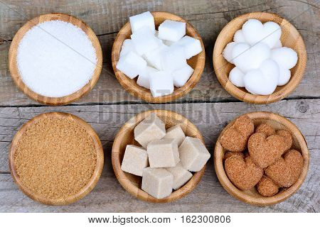 Variation types of sugar in a bamboo bowls on wooden table
