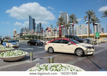 DUBAI UNITED ARAB EMIRATES - DECEMBER 10 2016: Dubai street with palm trees and modern high-rise buildings.