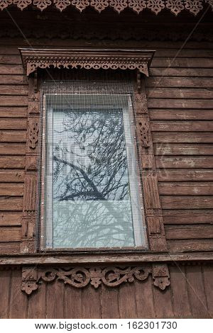 Window in a house in the city in Ukraine in the second half of the nineteenth century. In the window reflected sky and trees