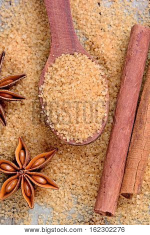 Beige sugar in a spoon and anise star with cinnamon on table