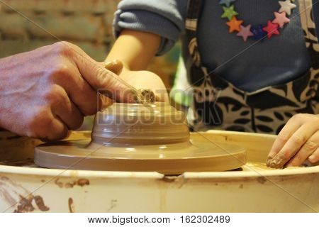 experienced master potter teaches the art of making pots of clay on the potter's wheel.