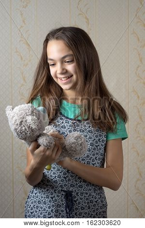 happy 11 year old girl holding a teddy bear and looking at him with love