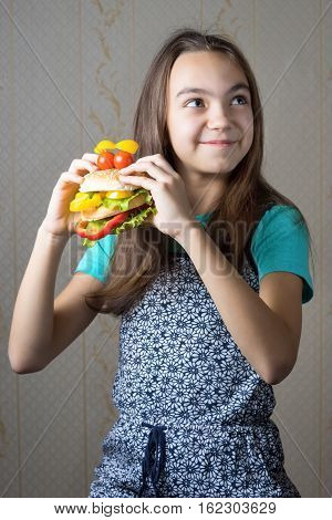 11 year old girl with a hamburger in hand looking up with the question of whether to eat junk food.