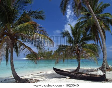 tropical white sand beach with a canoe