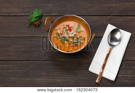 Vegan and vegetarian dish, spicy creamy tomato dahl soup bowl. Indian cuisine, masala hot meal on wood background. Eastern local cuisine restaurant food above view