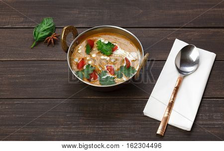 Vegan and vegetarian dish, spicy lentil dahl soup bowl. Indian cuisine, masala hot dal meal on wood background. Eastern local cuisine restaurant food above view