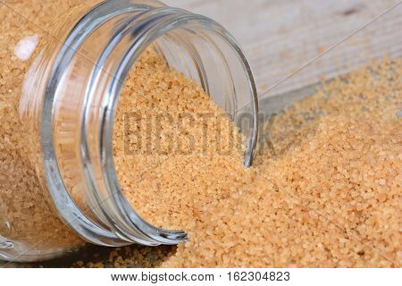 Jar with beige sugar on wooden table