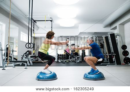 Beautiful fit senior couple in gym working out with weights and squatting at the same time poster