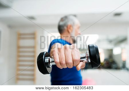 Senior man in sports clothing in gym working out with weights. Close up of hands.
