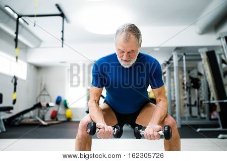 Senior man in sports clothing in gym working out with weights and squatting at the same time.