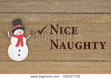 Old fashion Christmas message A retro snowman on weathered wood background with text Nice Naughty