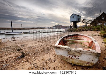 Old red rowing boat on the beach with a lookout tower behind at sunrise. Low tide showing tethered boats to a pontoon. Amazing dramatic skies and clouds.