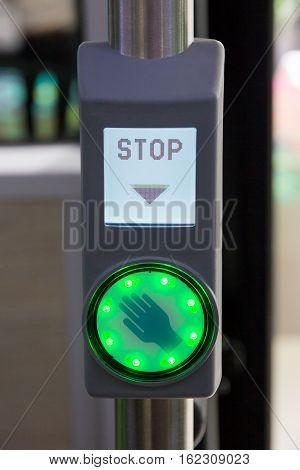 City bus illuminated stop sign button close up