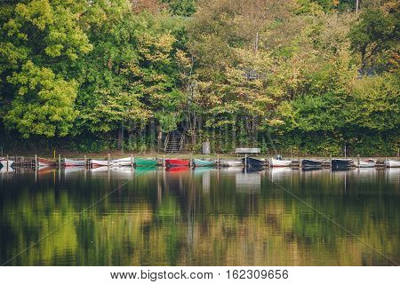 Boats On A Row In A Lake Surrounded By Green Trees