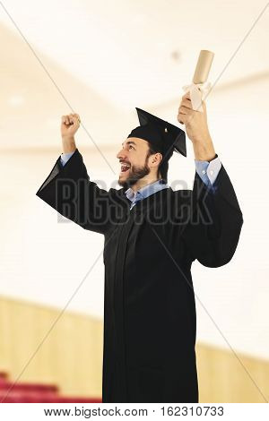 cheerful college graduate wearing gown at graduation ceremony