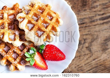 Round Belgian waffles with strawberries and icing on a white plate with copy space