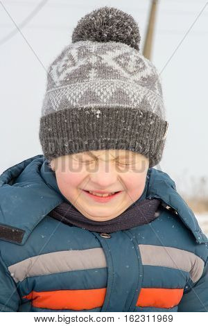 boy in a hooded jacket with his eyes closed covered in snow during a walk in the winter woods at sunset