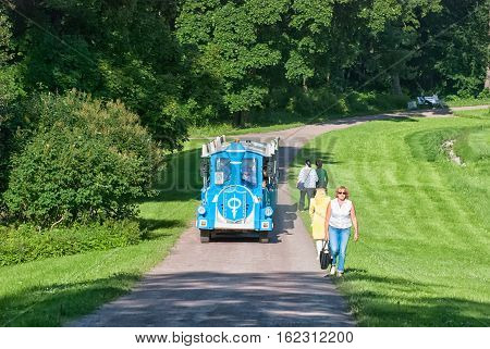 PETERHOF, SAINT - PETERSBURG, RUSSIA - JULY 14, 2016: People travel in excursion fun train in Alexandria, palace and park ensemble, last summer residence of the Russian Emperors from 1830 until 1917