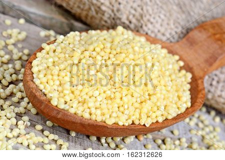 Millet seeds in a wooden spoon on table