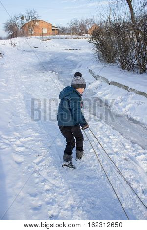 A young boy dressed for cold weather pulls a sled by a rope along in the snow