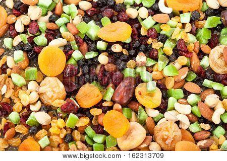 Background of mixed dried fruits (raisins, apricots, figs, prunes, goji, cranberries, blueberries, prunes) and nuts (almonds, hazelnuts, peanuts, cashews)