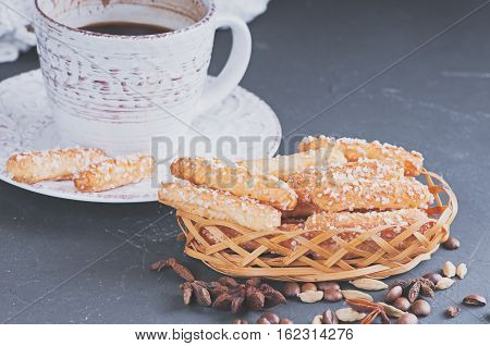 a sugar homemade biscuits piled in a wicker basket and a cup of hot coffee on a dark background haze filter