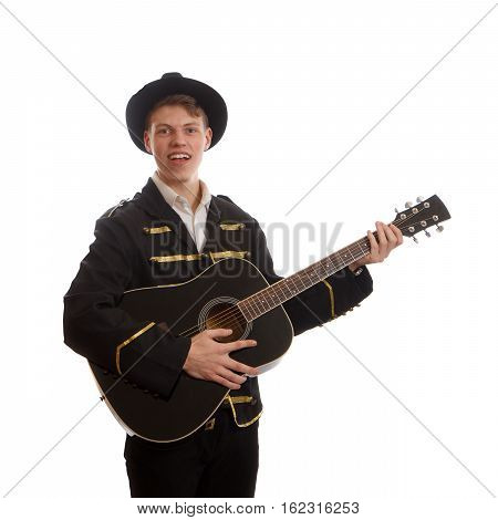 A young adult holding a black guitar