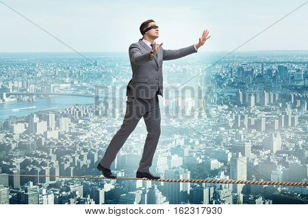 Man walking in tight rope blindfold