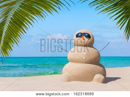 Positive sandy snowman in black eyeglasses and carrot nose at tropical ocean beach under palm leaves shade. Happy New Year and Merry Christmas travel destinations for tropical vacations concept