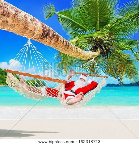 Santa Claus sunbathe in white cozy mesh hammock in shade of coconut palm tree at sandy ocean island beach. Happy New Year and Merry Christmas travel destinations for tropical vacations concept