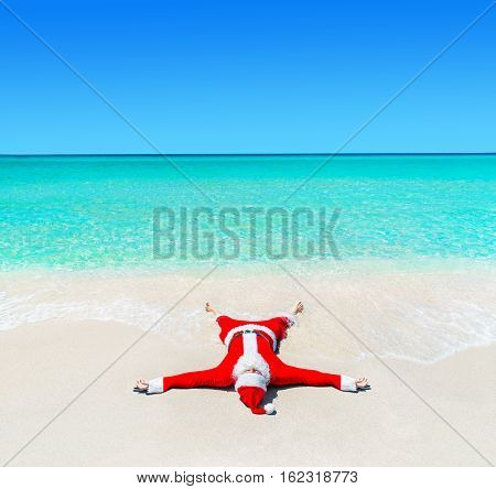 Santa Claus enjoy tanning at tropical ocean beach in turquoise water waves Christmas and New Year vacation destinations in hot countries concept