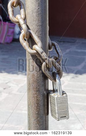 Vertical photo in color and shallow depth offield of a padlock holded by a chain in a cross-arm