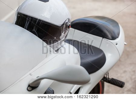 White sports motorcycle with a helmet parked on the roadside.