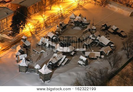 The scenery of the wooden Slavic village in full size with snow at night. View from above