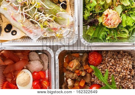 Healthy food background. Take away of natural organic meals in foil boxes. Fitness nutrition, eggs, meat, fresh vegetables and kasha buckwheat porridge. Top view, flat lay. Restaurant dishes delivery