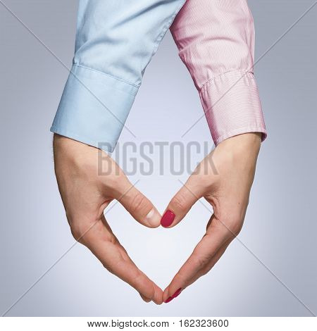 Man and woman holding hands in a shape of a heart isolated on whitebackground. Young couple in love