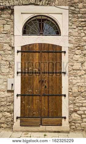 The entrance wooden door in an old Italian house